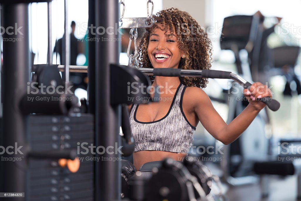 Curled hair woman working out at GYM club. stock photo