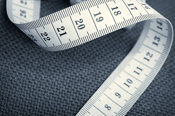 curled measuring tape on a gray canvas - customize stock pictures, royalty-free photos & images