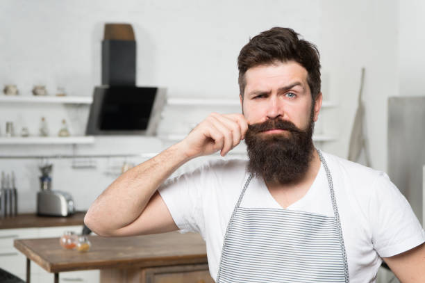 Curling his long moustache. Professional cook confident in his cooking skills. Bearded man during cooking in kitchen. Home-cooking and commercial cooking. The art of cooking stock photo