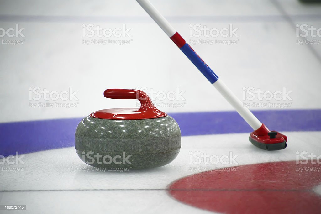 Curling stone and broom on the ice stock photo