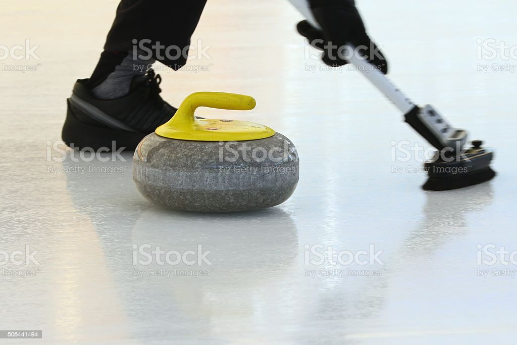 Curling stone and broom stock photo