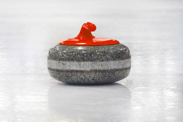 curling stones lined up on the playing field - granite rock stock photos and pictures