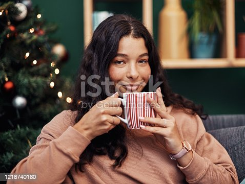 Shot of a beautiful young woman enjoying a warm beverage on the sofa during Christmas at home