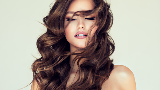 Curls of hair is freely flying in front of the face of young beautiful woman. Closed eyes and slightly opened mouth. Young brown haired woman  with voluminous, shiny and wavy hair  and perfect makeup. Beauty and style.