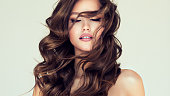 istock Curls of hair is freely flying in front of the face of young beautiful woman. Calmness and beauty. 1267002400