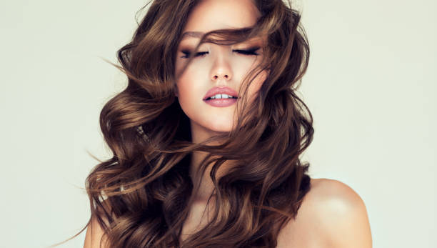 Curls of hair is freely flying in front of the face of young beautiful woman. Calmness and beauty. stock photo