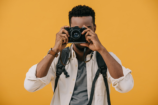 curly african american photographer covering face with digital camera isolated on orange