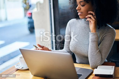 istock Curly African-American in a gray jacket using free 5G wireless sitting in cafe 694176922