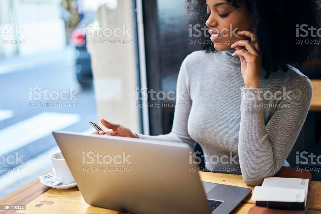 Curly African-American in a gray jacket using free 5G wireless sitting in cafe stock photo