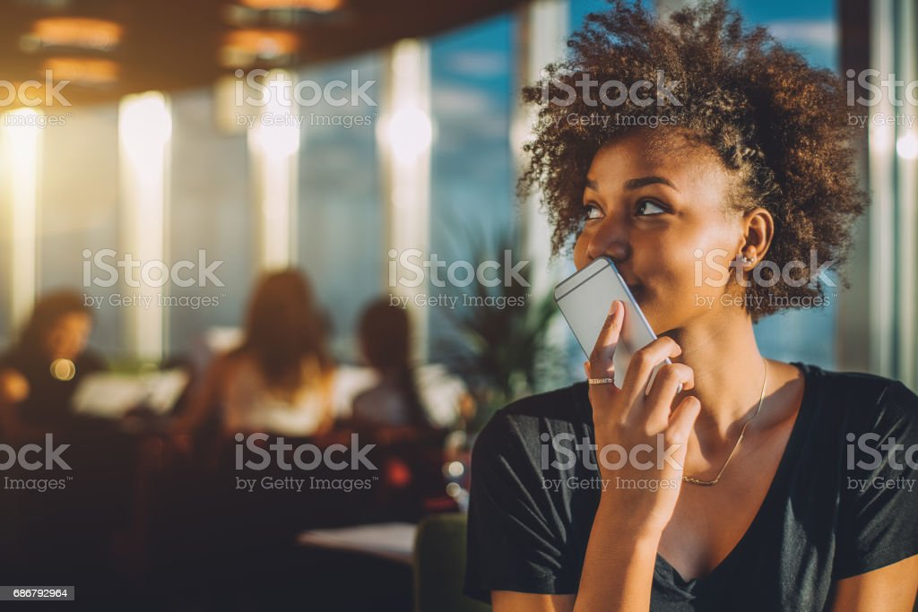 Curly black girl using her phone as voice recorder Young curly black female in luxury office space recording audio message via her smartphone, afro american teenage curly girl using her cell telephone as recorder to send voice message to her mother Adult Stock Photo