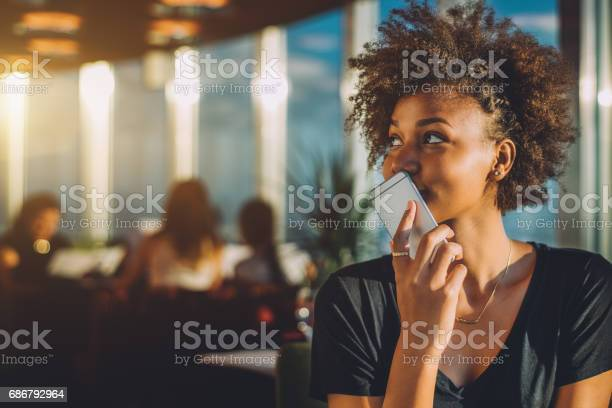Curly Black Girl Using Her Phone As Voice Recorder Stock Photo - Download Image Now