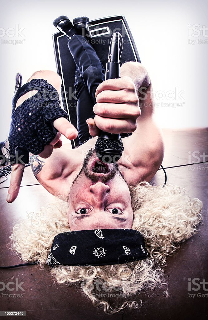 Curly Blond Haired Rocker Lying Upside Down on Floor, Singing royalty-free stock photo