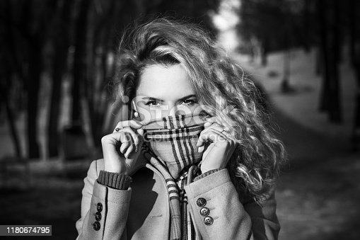 1051172208 istock photo Curly blonde woman in winter park 1180674795