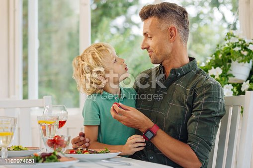 Curly blonde-haired son speaking with daddy while eating lunch