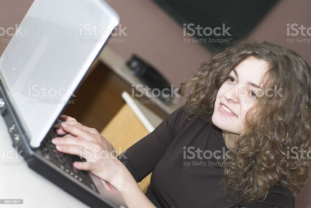 Curly brown haired woman working on her laptop royalty-free stock photo
