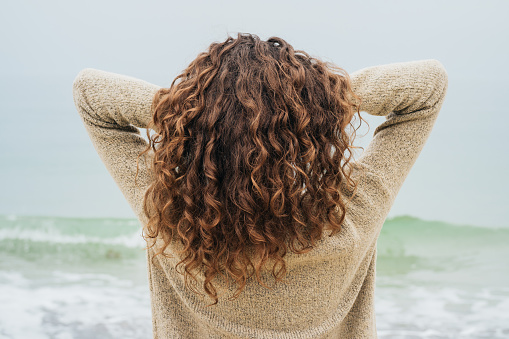 istock Curly brunette in a sweater on the coast 537543842