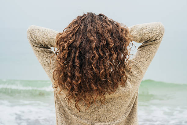 Curly brunette in a sweater on the coast Curly brunette in a sweater on the coast faces the sea and straightens hair, view from the back curly hair stock pictures, royalty-free photos & images