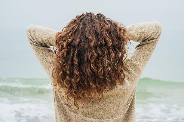 ricci bruna in una maglia un coste - capelli ricci foto e immagini stock