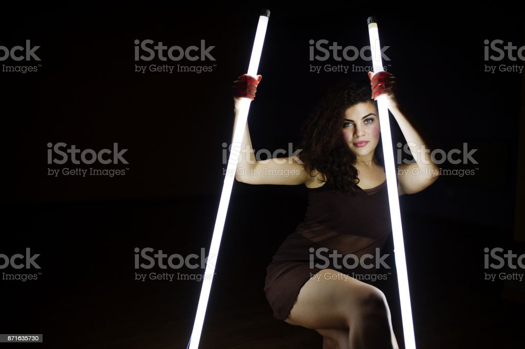 Curly brunette plus size model with two long led lamp at black room. stock photo
