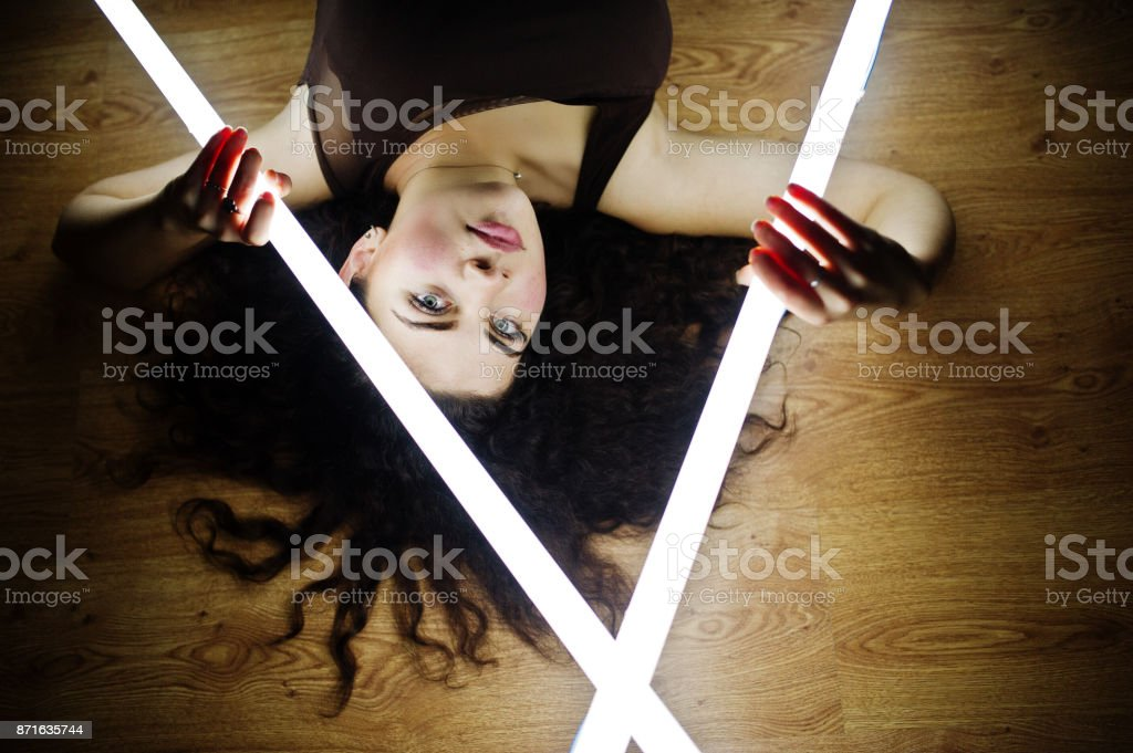 Curly brunette plus size model with two long led lamp at black room lying on flat. stock photo
