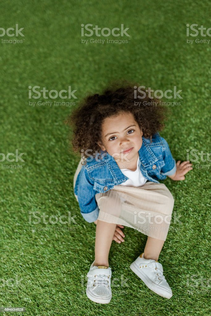 curly girl resting on lawn Lizenzfreies stock-foto