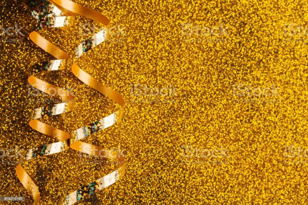 Curly golden serpentine on glitter background stock photo