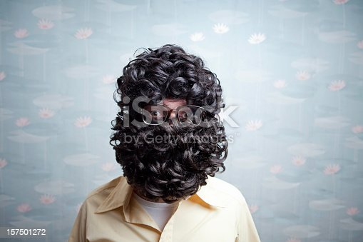 A man's black curly beard and hair completely cover his face with the exception of his eyes and glasses.  His eyes look surprised.  Vintage retro wallpaper in the background.  Horizontal with copy space.