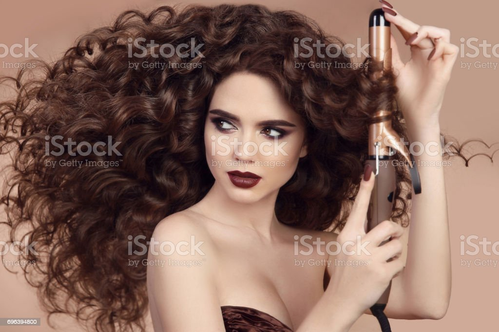 Curly Hair. Hairstyling. Beautiful Brunette Woman portrait With long wavy hair Ironing It, using Curling Iron. Sensual girl with Gorgeous Healthy Smooth Hair. Perfect Curls. stock photo