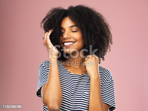 Studio shot of a beautiful young woman posing with her hands in her hair