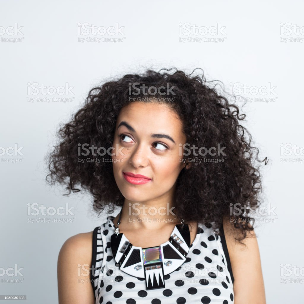 Curly hair woman staring at copy space Close up of beautiful mixed race woman with curly hair looking away at copy space on white background 20-24 Years Stock Photo