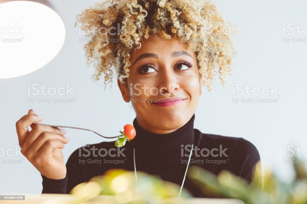 Curly hair young woman eating salad stock photo