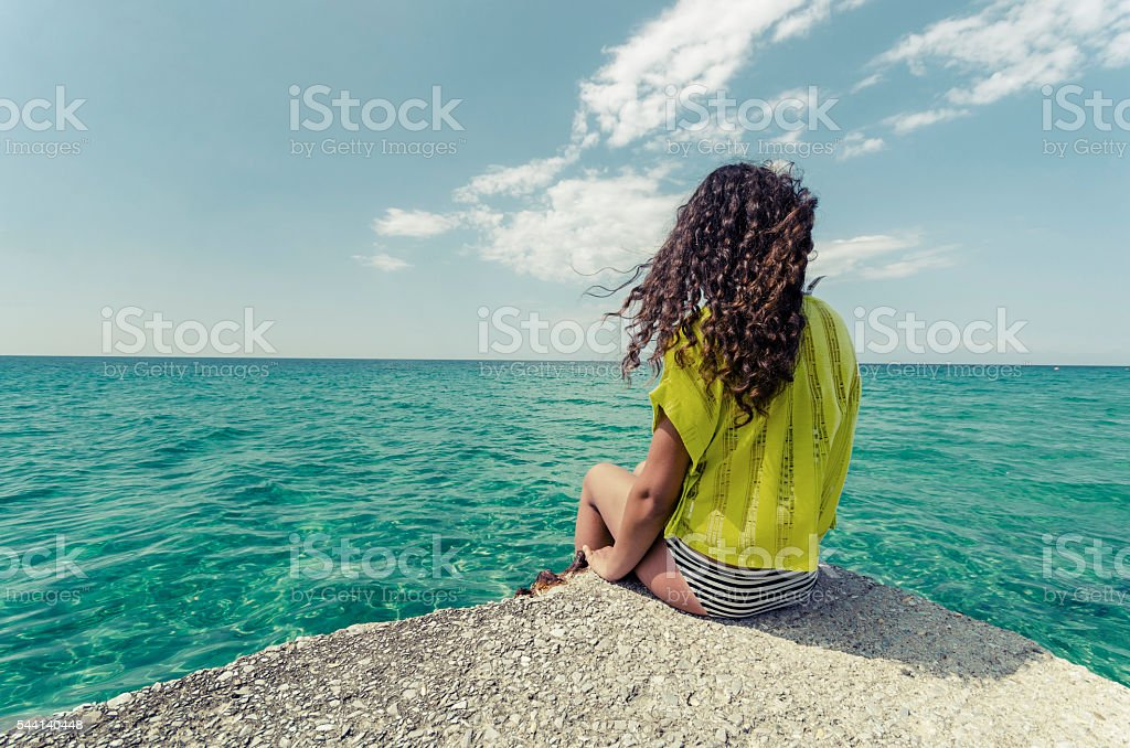 Curly hair young woman is enjoing calm ocean water surface stock photo
