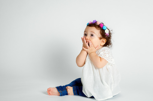 istock A curly haired, brunette baby wearing a colorful, floral headband sits on a white background with hands to her mouth.  She is blowing kisses but looks surprised. 693176466