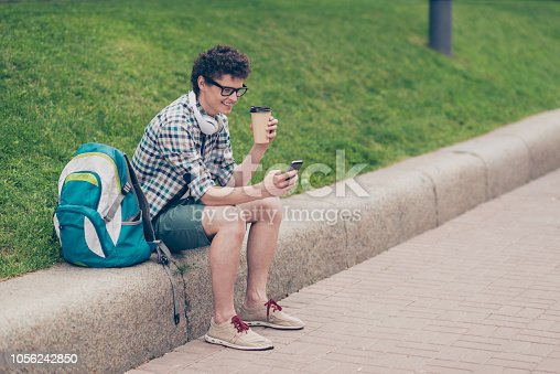 istock Curly haired cute attractive smiling handsome guy with smartphone, headphones wearing casual shirt and glasses, outside in park, chatting texting drinking take-away paper-cup of coffee tea 1056242850