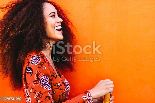 Side view shot of attractive female with soap bubbles. Young woman having fun against orange background.