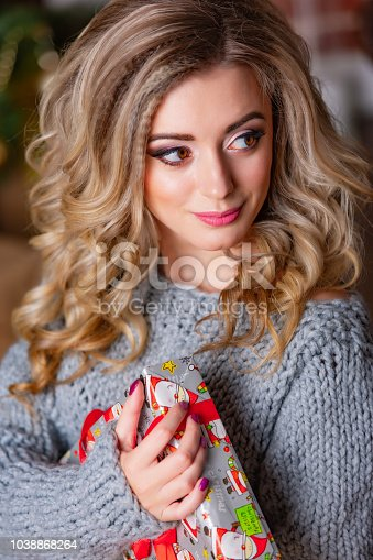 455111881istockphoto curly haired woman in a knitted dress with a beautiful smile holds New Year's gift in her hands. 1038868264