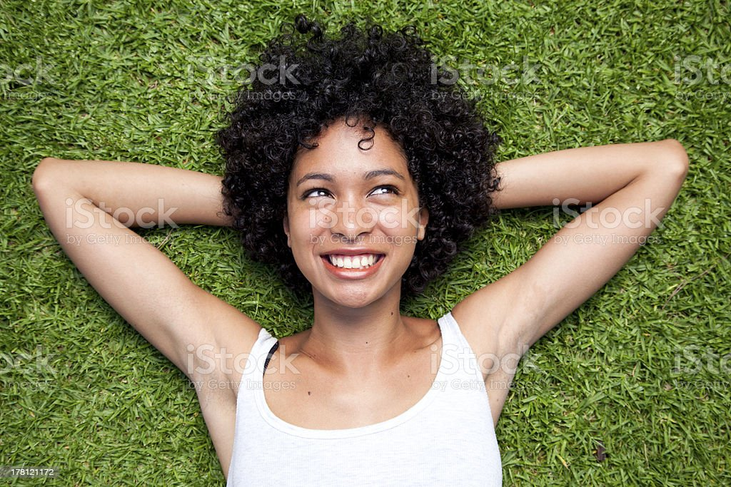 Curly haired woman smiling white laying in the grass stock photo