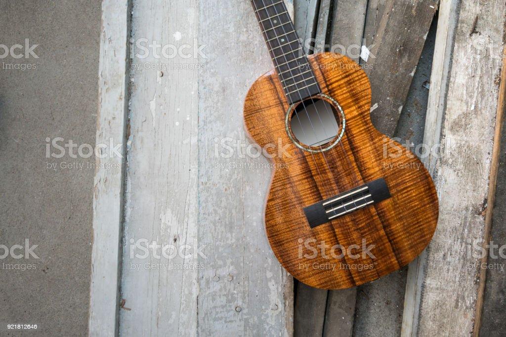 Curly koa ukulele gloss finished against wooden background. Selective focus stock photo