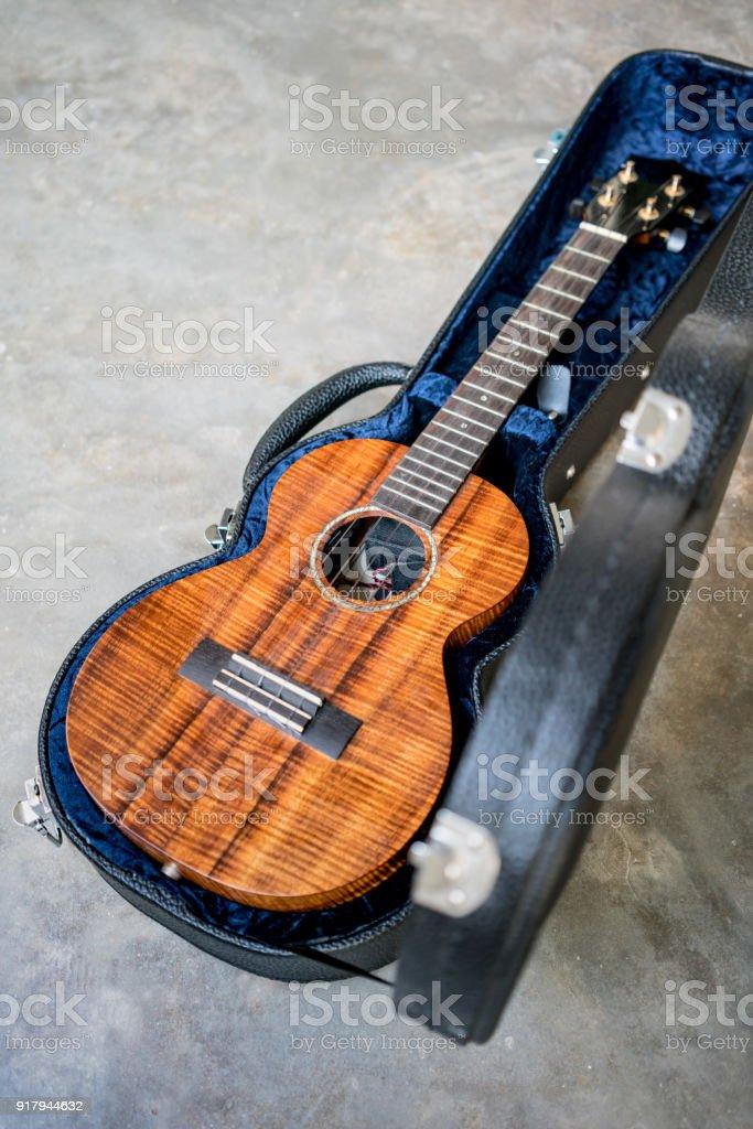curly koa ukulele gloss finished and hard case on concrete floor background stock photo