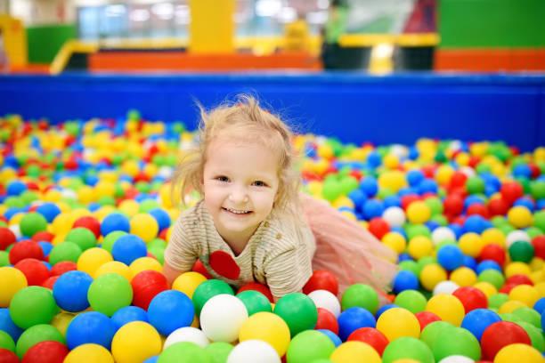 Rizado niña divirtiéndose en el hoyo de la bola con las bolas de colores - foto de stock