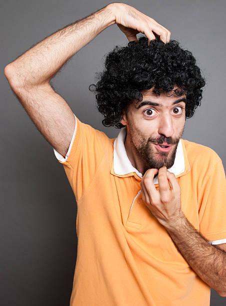 Curly hombre y su imitación de mono cara - foto de stock