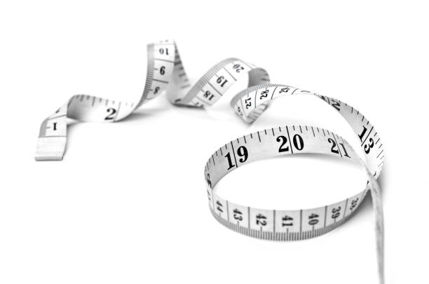 Curly measure tape, dieting or weight loss theme Curly measure tape, dieting or weight loss theme, isolated on white background. Black and white measure tape, top view. tape measure stock pictures, royalty-free photos & images