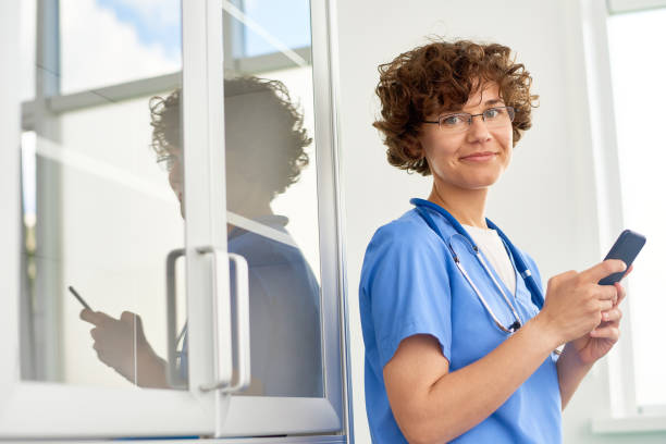 curly physician using smartphone - nurse on phone stock photos and pictures