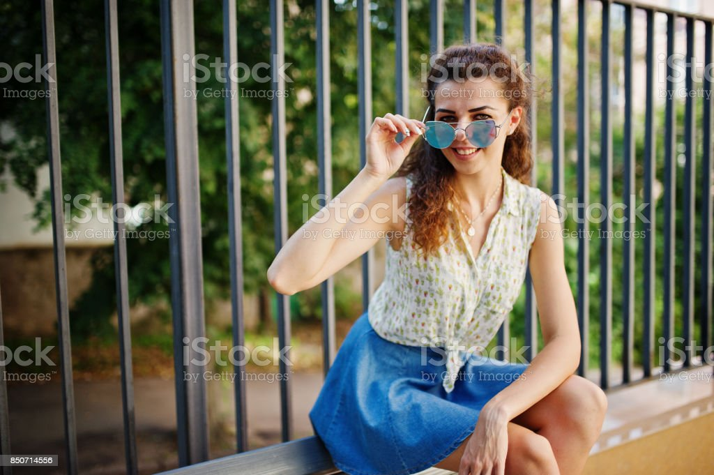 Curly stylish girl wear on blue jeans skirt, blouse. stock photo