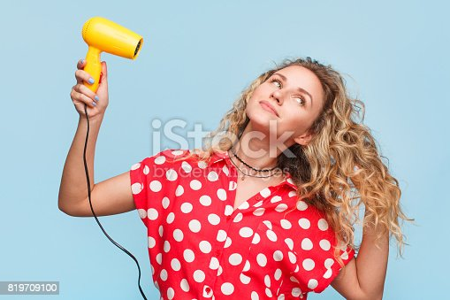 Young woman in casual clothing posing on blue background using dryer.