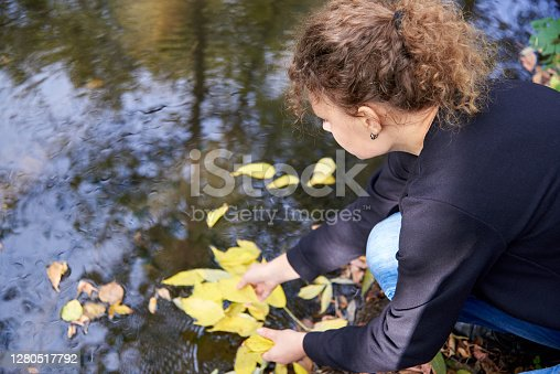 Curly woman sits near the river with yellow leaves in autumn.