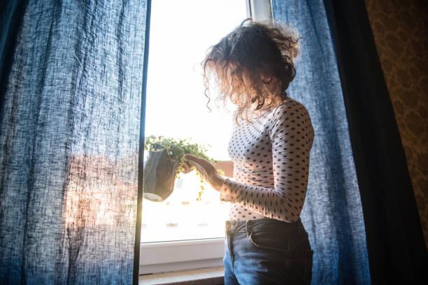 curly woman taking care of her plants - showus стоковые фото и изображения