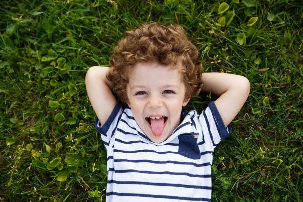 Curly-haired boy lying on grass Curly-haired boy in striped t-shirt with hands behind head lying on grass smiling and sticking out tongue. protruding stock pictures, royalty-free photos & images