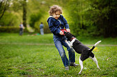 Curly blond boy having fun playing with a black and white dog on a green lawn