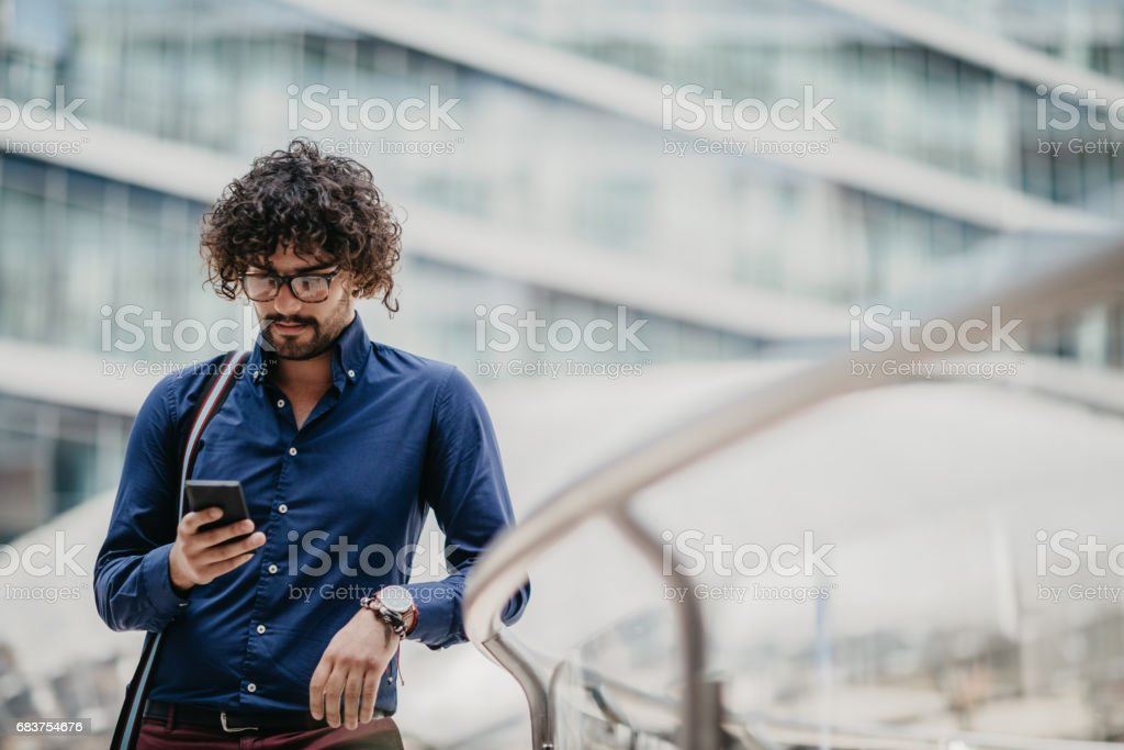 Curly-haired business person is using smartphone to check social media